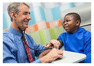 Marshall Jones, right, laughs with Dr. John Barcia of UVA Children's Hospital (Coe Sweet/UVA Health System via AP)